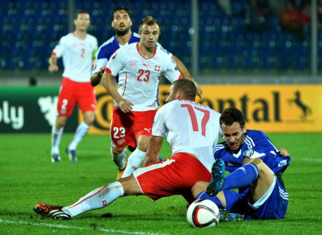 Der Schweizer Pajtim Kasami (L)mit San Marino's Abwehrspieler Cristian Brolli während dem UEFA Euro 2016 Gruppe E qualifying football match Sam 14. Oktober 2014 at the Olympic Serravalle stadium in San Marino. AFP PHOTO / ALBERTO PIZZOLI