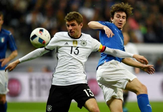 DFB-Spieler Thomas Müller im Zweikamp mit Matteo Darmian während des Freundschaftsspiels Deutschland gegen Italien(4-1) in München am 29.März.2016. / AFP / PATRIK STOLLARZ